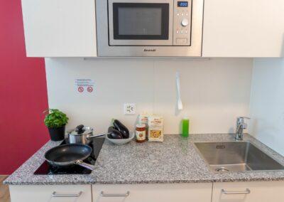 Modern und vollständig eingerichtete Küchenzeile mit Pfannen und Geschirr